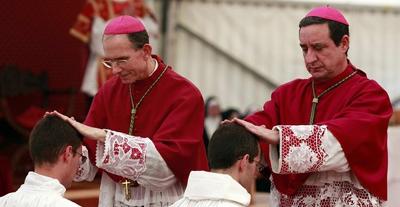 Bishop Tissier de Mallerais and Bishop de Gallareta gesture during a priests ordination ceremony